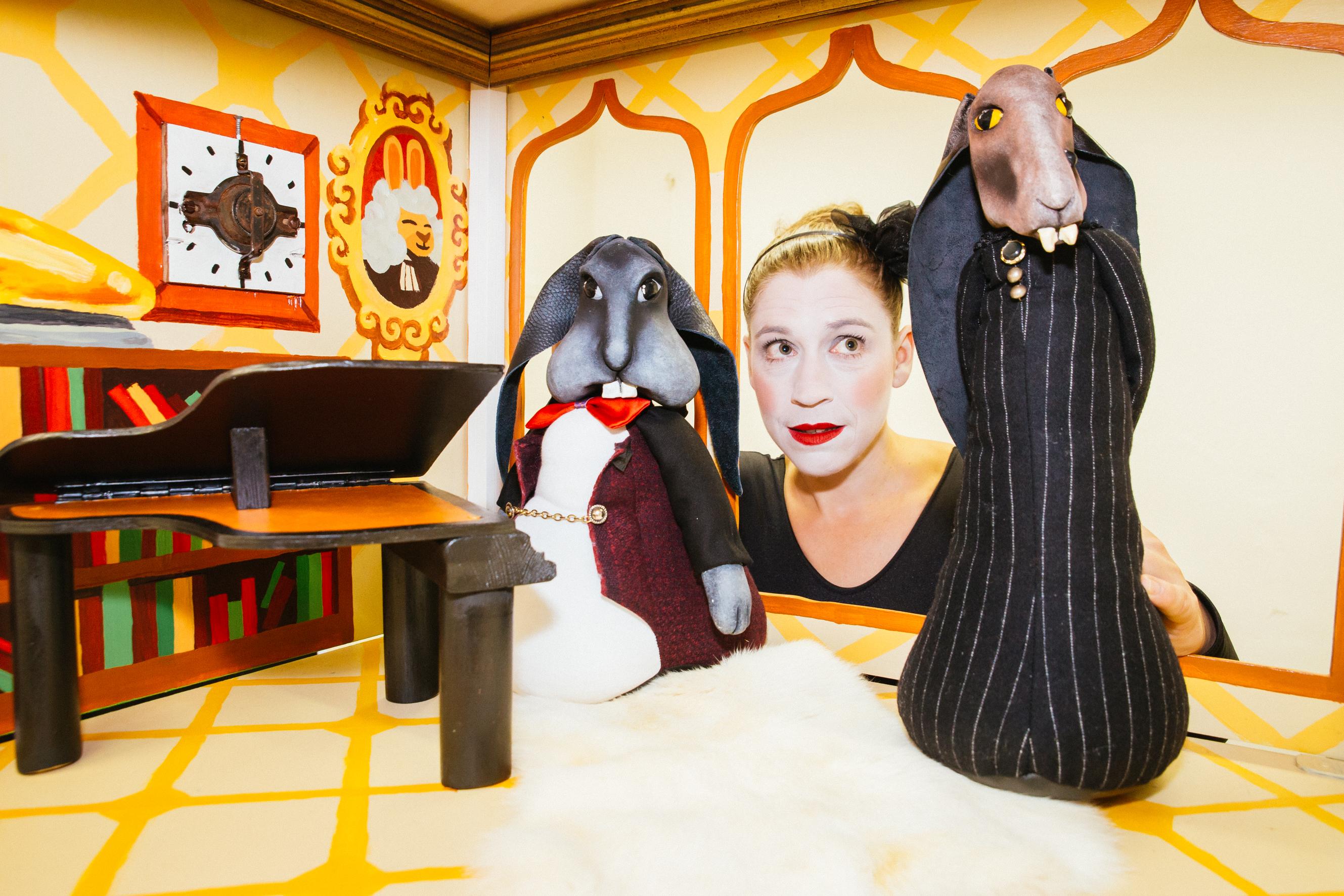 Pressefoto der Figurentheater Inszenierung 'Der Sängerkrieg der Heidehasen' mit einer Szene im Singzimmer von Herrn Direktor Wackelohr und dem Minister für Hasengesang. Im Hintergrund spielt Julia Raab die Figuren.; Foto: Julia Fenske