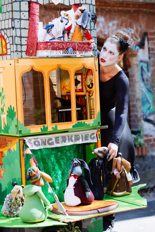 Figurenspielerin Julia Raab neben dem Bühnenwagen Ihrer Figurentheater-Inszenierung 'Der Sängerkrieg Der Heidehasen'