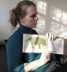 Theaterpädagogin Anja Schwede hält ein Buch in die Höhe, das einen Hund in Form eines Labyrinths zeigt.