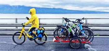 Jemand auf einem Fahrrad zieht einen 'hinterher'-Anhänger, beladen mit mehren Fahrrädern.