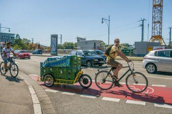 Ein Mann auf einem einfach Fahrrad zieht einen carlacargo Fahrradanhänger, beladen mit sehr vielen Gemüsekisten.