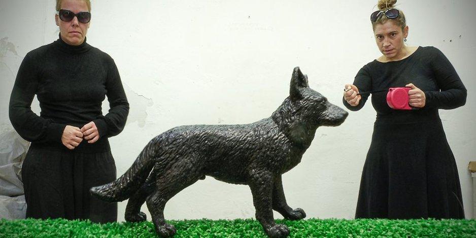 Theaterpädagogin Anja Schwede & Figurenspielerin Julia Raab posieren für Ihre neue Figurentheaterproduktion zum Thema Depressionen hinter einem übergroßen schwarzen Hund aus Kunststoff.
