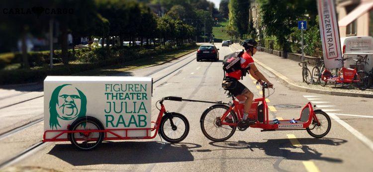 Ein Lastenrad mit Fahrer zieht einen dreirädrigen Anhänger, auf dem eine große Kiste geladen ist. Darauf zu sehen ist das Konterfei der 'Dicken' und der Schriftzug 'Figurentheater Julia Raab'. Das Originalbild stammt von carlacargo.