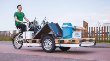 Ein Mann auf einem Urban Arrow Lastenrad, beladen mit 2 Europaletten und allerhand Kram.
